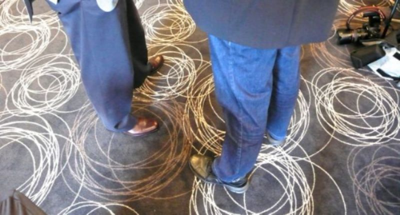 The carpet ripples around the feet of John Ruggie and Phil Clothier